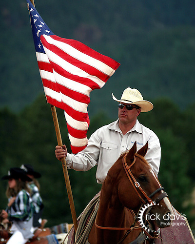 Colorado Pro Rodeo Association pick up man Matt Carrol posts the colors during the rodeo grand entry parade in Woodland Park, Colorado on July 13, 2003.