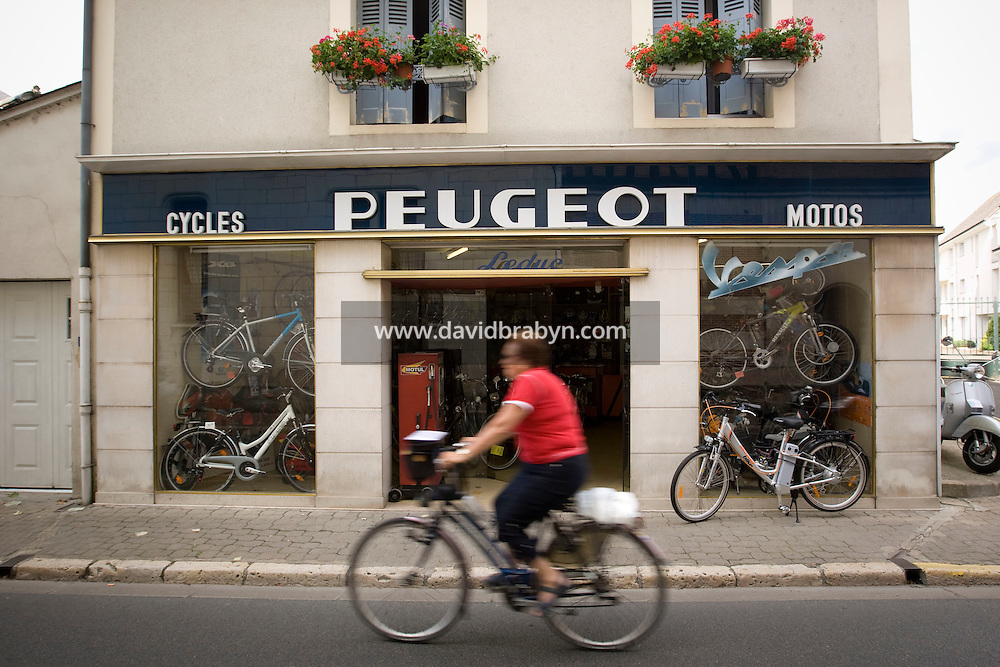 A woman rides past the Leduc bicycle store in Amboise in France, 25 June 2008.