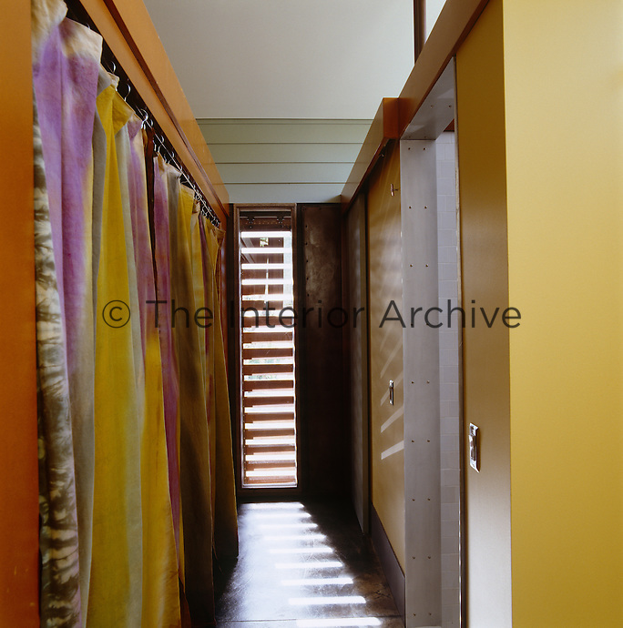 Tie-dyed curtains cover storage cupboards that line the hallway