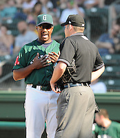 Manager Billy McMillan (51) of the Greenville Drive discusses a call with home plate umpire Ben Leake during a game against the Augusta GreenJackets on April 10, 2011, at Fluor Field at the West End in Greenville, South Carolina. (Tom Priddy / Four Seam Images)