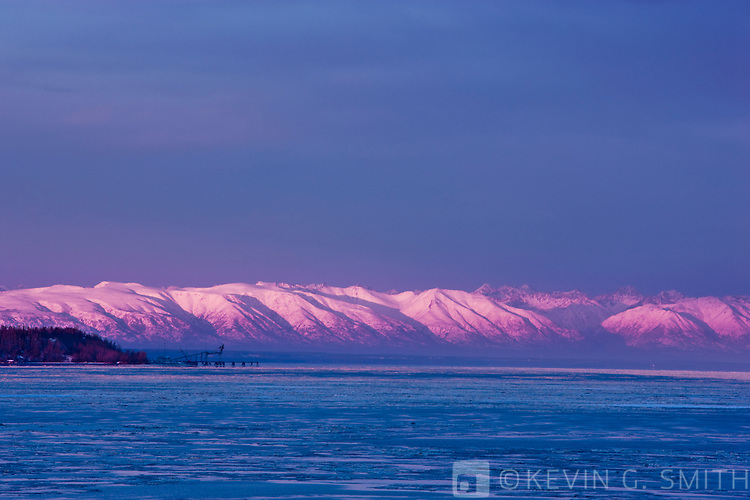 Photo of the Point Mackensie loading dock at sunset, aplenglow on the Talkeetka Mountains, taken from Earthquake park, winter, Southcentral  Alaska, USA.