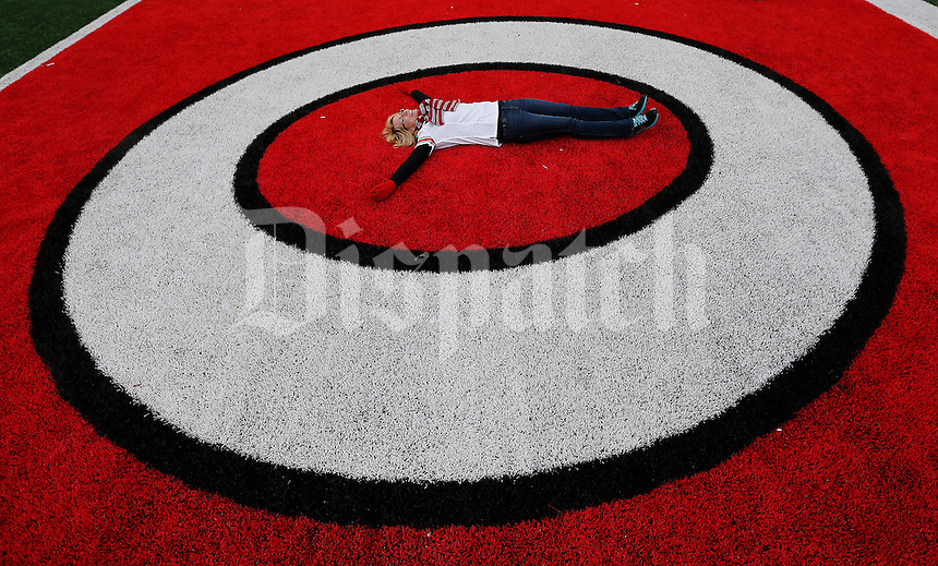 Marie Dodig, of Parma, OH, lays in the center of the O as she poses in the end zone while her husband Bob Dodig takes a photograph before the Ohio State Football National Championship Celebration at Ohio Stadium, Saturday morning, January 24, 2015. More than 40 thousand fans packed the lower stands in the stadium to celebrate the National Championship win with the football team. (The Columbus Dispatch / Eamon Queeney)