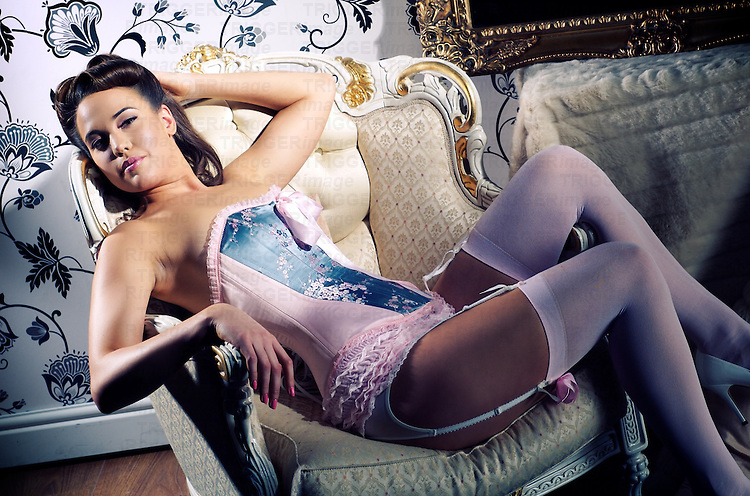 Young female in lingerie reclines in a chair.