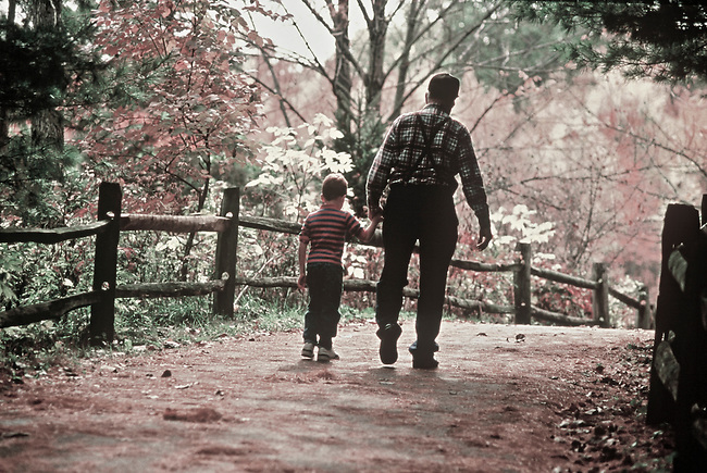 A grandfather and grandson walking amoung the fall foliage in an urban park in Columbus, Ohio.
