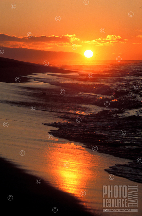 A North Shore beach lit up by a beautiful sunset as waves wash up