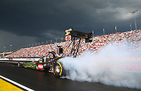 Aug. 31, 2013; Clermont, IN, USA: NHRA top fuel dragster driver Terry McMillen does a burnout under dark clouds of an approaching storm during qualifying for the US Nationals at Lucas Oil Raceway. Mandatory Credit: Mark J. Rebilas-