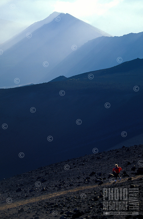 A woman getting her running workout on the laval fields of Halekala Crater in the National Park on Maui.