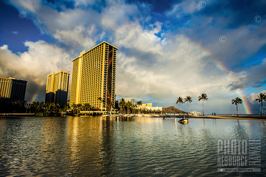 A rainbow touches down on both sides of the Rainbow Tower in Waikiki, with Diamond Head in the distance, O'ahu.