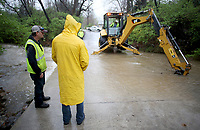 NWA Democrat-Gazette/DAVID GOTTSCHALK Shem Davis, with the city of Fayetteville Transportation, uses a backhoe Tuesday, March 27, 2018, to clear debris under a low water bridge on Frisco Avenue in Fayetteville. Heavy rains in Northwest Arkansas caused closure of some streets.