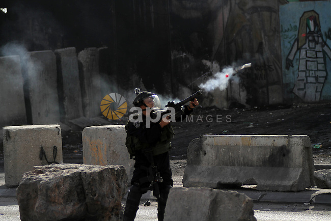 A member of Israeli security forces fires tear gas towards Palestinian protesters during clashes with Israeli security forces following a protest against Israeli restrictions to Al-Aqsa Mosque in Jerusalem, at the Qalandia checkpoint near the West Bank city of Ramallah, November 14, 2014. Israel eased age restrictions for Friday prayers at Jerusalem's flashpoint Al-Aqsa mosque for a second straight week, allowing tens of thousands to attend despite high tensions following a wave of violence. Photo by Shadi Hatem