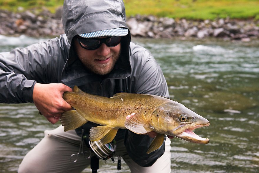 A fly fisherman holds a New Zealand brown trout.