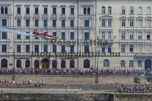 People watch aerobatic world champion Zoltan Veres of Hungary flie with his airplane during an air show above river Danube crossing central Budapest, Hungary on May 01, 2013. ATTILA VOLGYI