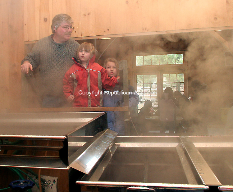 WOODBURY, CT - 10 MARCH 2007 - 031007JW03.jpg -- Paul Badger of Watertown and his daughters Anne Badger age 7 and Emily Badger age 9 look through the steam coming from the evaporator making Maple Syrup Saturday afternoon during a demonstration at Flanders Nature Center.  Jonathan Wilcox Republican-American