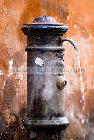 Old big nose (Er Nasone) water fountain against orange wall, Rome, Italy