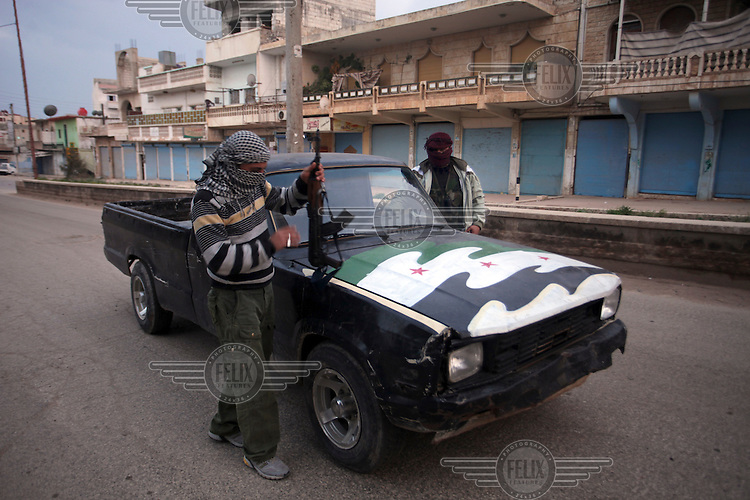 Free Syrian Army fighters are seen at dawn in Binnish, a small frontline town northeast of Idlib. The civilian population here awaits their fate as Syrian military forces amass nearby.