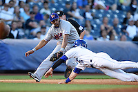Midland RockHounds third baseman Jefry Marte (34) attempts to tag Tyler Massey (5) sliding into third safely during a game against the Tulsa Drillers on May 31, 2014 at ONEOK Field in Tulsa, Oklahoma.  Tulsa defeated Midland 5-3.  (Mike Janes/Four Seam Images)
