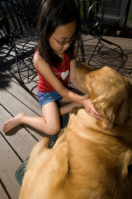 Chinese-American girl with her golden retreiver on the deck