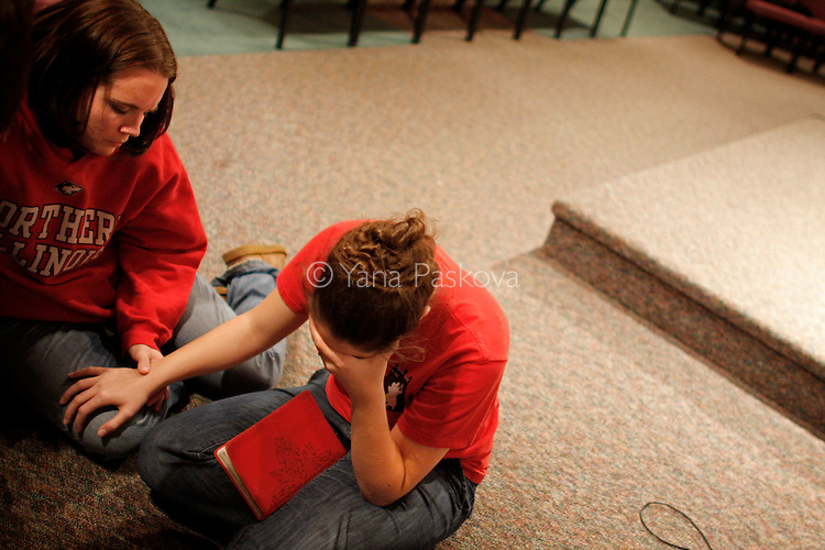 (R-L) NIU student Suzanne Mauhar, 22, and Secretary for Finance and Facilities on campus Jessica Best, 22, cry and pray at  the Harvest Bible Chapel, which held a vigil after a gunman's shooting rampage killed 5 people and injured 16 others at Northern Illinois University in Dekalb, Illinois, on February 14, 2008. (Photo by: Yana Paskova for The New York Times)..Assignment ID: 30057202A...