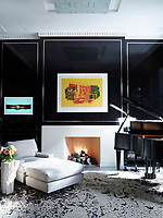 In the library, the walls are panelled with nickel-inlaid ebonized mahogany and the rug is by Beauvais Carpets. An elegant armchair and ottoman are set to one side of the open fireplace with a baby grand piano on the other.