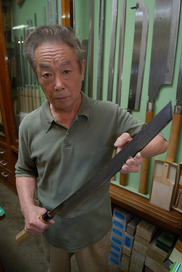 3rd generation knife shop owner Azuma Masahisa holding a tuna knife in his shop.