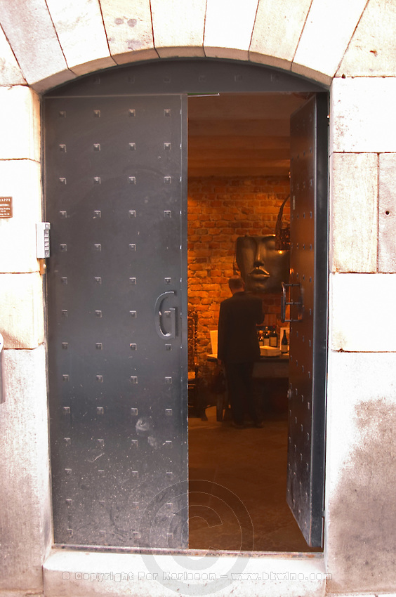 The iron cellar door with a wrought iron G leading in to the reception with a man standing there At the wine cellar storage company Grappe in Stockholm where private individual s can store and age wine bottles. Källaren Grappe Wine Storage Cellar, Stockholm, Sweden, Sverige, Europe
