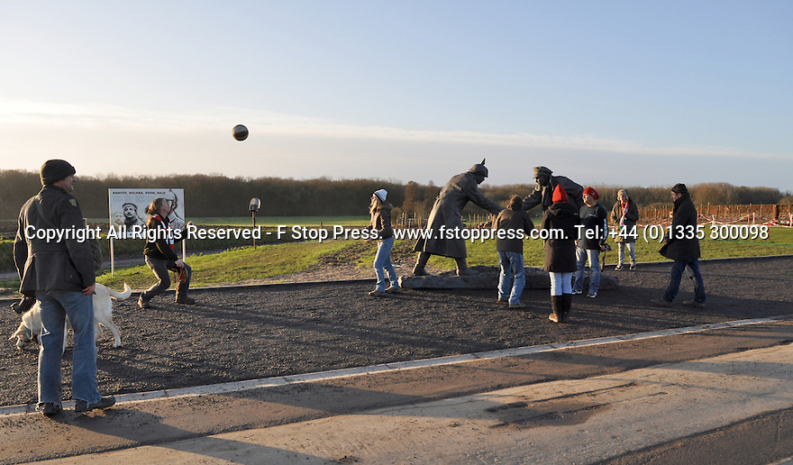 """25/12/14<br /> <br /> People play football by a sculpture depicting two WW1 soldiers playing football during the famous Christmas Day truce in the field near Messine, Belgium, close to where the match was played in Flanders, Belgium.<br /> <br /> The sculpture, made in England, arrived in Flanders on Christmas Eve, and was first displayed in the town centre before being taken to the spot where the match was played. <br /> <br /> Sculpted by Andy Edwards the work is entitled 'All Together Now', recalling the song by the band The Farm - which was inspired by the truce. <br /> <br /> Chris Butler said: """"Castle Fine Arts are proud to have cast a number of war memorials over the years. We are honoured to support this sculpture for peace. I believe it will touch the hearts of millions.""""<br /> <br /> <br /> """"It will be a symbol of peace and hope and a call for a renewed worldwide cessation of violence in honour of those brave boys who 'joined together and decided not to fight'"""".<br /> <br /> <br /> The statue depicts the meeting of a British and a German soldier over a football, deep in the mud between the lines on that first Christmas of the war. The soldiers appear to be shaking hands but  are not not quite touching, forming a space in which a visitor can insert their own hand to complete the union.  A chance for a moments reflection on how far we are from true peace and brotherhood and the part each of us has to play in that dream. We want the work to stand as both a celebration of this inspirational and heroic event and as symbol of hope and peace. <br /> <br /> The project was instigated some years ago, with the support of the Football Asscociation (FA), as football's contribution to the First World War commemorations. <br /> <br /> All Rights Reserved - F Stop Press. www.fstoppress.com. Tel: +44 (0)1335 300098"""