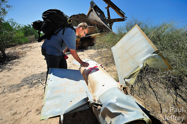 Johnny Thomsen, a Danish explosive ordnance disposal technician, marks a Russian-built SA3 missile on June 15 at a former Libyan Air Force site outside Misrata, the besieged Libyan city where civilians and rebel forces are surrounded on three sides by forces loyal to Libyan leader Moammar Gadhafi. Several missiles here were damaged in a NATO air strike, and a team from the ACT Alliance, concerned about the safety of civilians traveling a nearby road, investigated the site and marked which items need to be safely removed. Thomsen is marking this missile for removal as it still contains its warhead. Thomsen works with the humanitarian mine action program of DanChurchAid, which is a member of the ACT Alliance.  Photo by Paul Jeffrey/ACT Alliance.