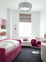 A teenager's bedroom in pink and white. An upholstered bed has built-in storage whilst an Arne Jacobsen Swan chair faces a dressing table unit. A patterned blind and a grey carpet complete the picture.