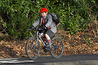 Josh  riding Islabike  bicycle on shared pavement / cyclepath in Hall Grove School uniform with school backpack ..Virginia Water , Surrey   February 2008..