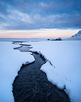 Small river running through snow on Skagsanden beach, Flakstadøy, Lofoten Islands, Norway