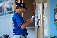 Durham Bulls manager Jared Sandberg (22) checks the lineup prior to the game against the Charlotte Knights at BB&T BallPark on July 4, 2018 in Charlotte, North Carolina. The Knights defeated the Bulls 4-2.  (Brian Westerholt/Four Seam Images)