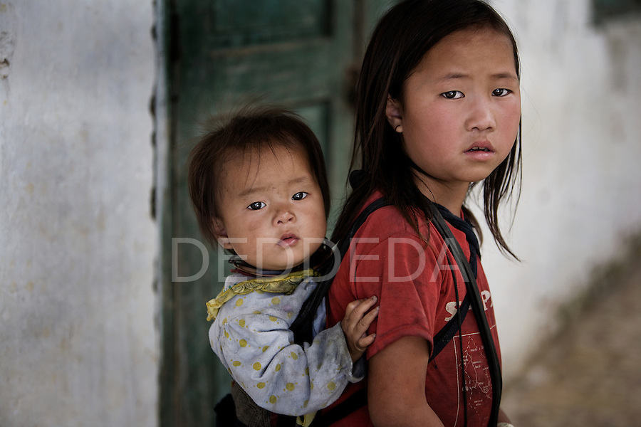 Local village children near rural Sapa, Vietnam. Older children are often the main caregivers of their younger siblings, usually carrying them on their backs throughout the day.