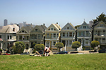 YOUNG WOMEN RELAX on GRASS in FRONT of VICTORIAN HOMES:(aka)PAINTED LADIES<br />