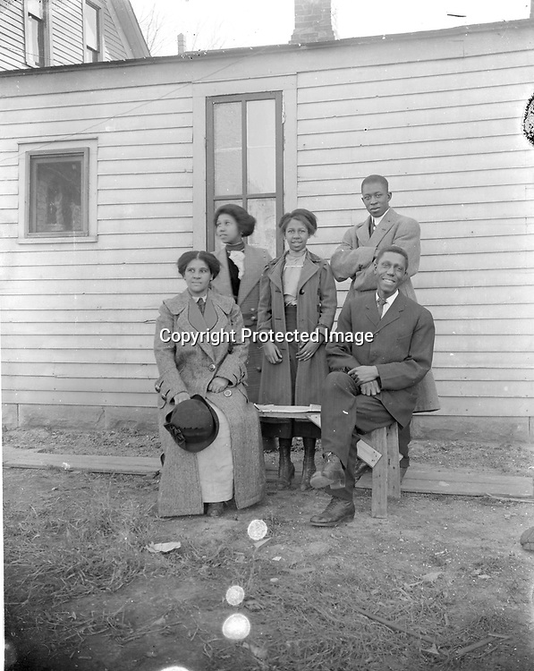 COLLEY AND MALONE FAMILIES. Walter R. Colley (1871-1970) is pictured at right, with his son-in-law Clyde Malone (1890-1951) standing behind him. Colley's wife Lula (1875-1958) shared the bench with her husband; between them stood their daughter Izetta (1892-1966). Clyde was 20 and Izetta 18 when they married in 1910, around the time this photograph was taken. As Clyde Malone wrote in 1946, &quot;After graduation from high school, I was fatally bitten by the matrimonial bug and deluded Miss Izetta Colley, of the Missouri Colleys, into saying 'I do', (and she has for lo' these many years).&quot; Their marriage lasted over 40 years until Clyde's death in 1951. <br /> <br />  Clyde Malone, standing at right, was born in Lincoln to Frank and Pency Malone. His father was a plasterer. Beside him is his wife, Izetta, whose parents, Lulu and Walter Colley, moved their family from Lexington, Missouri, to Lincoln in 1905. Father and son-in-law held service jobs typical of those available to black men in Lincoln in the first two decades of the 20th century--porter, janitor, waiter--before partnering to operate a grocery store in 1920-1921. <br /> <br /> Clyde then attended the University of Nebraska and graduated in 1925. Clyde and Izetta left Lincoln for about a decade while he worked as a district manager for an insurance company and then at a community center in Minneapolis, before returning to work at Lincoln's Urban League. He became executive director in 1943 and served until his sudden death in 1951. The Urban League was renamed Clyde Malone Community Center in his memory. Izetta was director of music at Quinn Chapel and played organ and sang at Lincoln's other black churches<br /> <br /> Photographs taken on black and white glass negatives by African American photographer(s) John Johnson and Earl McWilliams from 1910 to 1925 in Lincoln, Nebraska. Douglas Keister has 280 5x7 glass negatives taken by these photographers. Larger scans available on request.