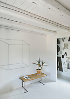 A functional, white room with a painted beamed ceiling and floorboards. A pot plant stands on a simple wooden table.