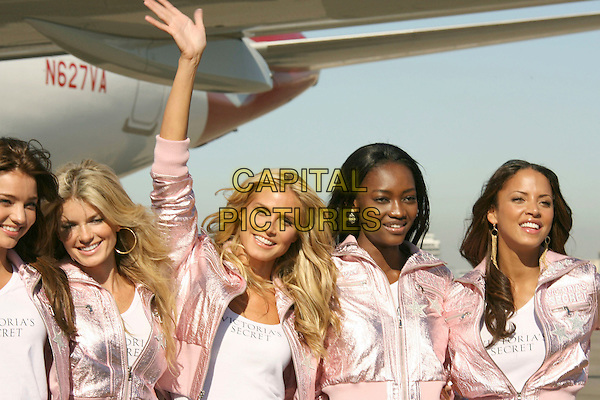 VICTORIA'S SECRET MODELS.Selita Ebanks, Adriana Lima, Alessandra Ambrosio, Heidi Klum, Izabel Goulart..Victoria's Secret Fashion Show Heads to Los Angeles as the models arrive on Virgin America at the Los Angeles International Airport, Los Angeles, California, USA,.12 November 2007.half length matching pink jackets jeans arm raised up pointing.CAP/ADM/RE.©Russ Elliot/AdMedia/Capital Pictures.