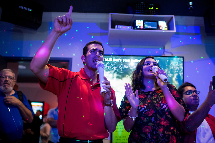 "UNITED STATES - AUGUST 23: Rep. Ruben Kihuen, D-Nev., sings Journey's ""Don't Stop Believin' "" with Lynette Hull, president of the UNLV Young Democrats, during the ""Karaoke with Kihuen"" event at Go Go Karaoke in Las Vegas on Wednesday, Aug. 23, 2017. The event was organized by the UNLV Young Democrats. (Photo By Bill Clark/CQ Roll Call)"