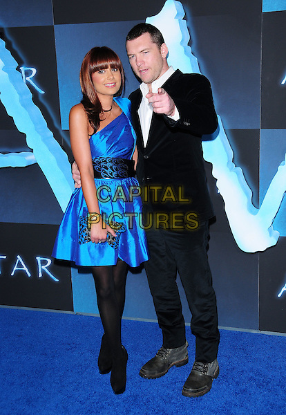 NATALIE MARK & SAM WORTHINGTON.The Twentieth Century Fox World Premiere of Avatar held at The Grauman's Chinese Theatre in Hollywood, California, USA. .December 16th, 2009.full length couple blue silk satin one shoulder dress black suit jacket clutch bag leopard print feather pattern waistband tights hand pointing .CAP/RKE/DVS.©DVS/RockinExposures/Capital Pictures.