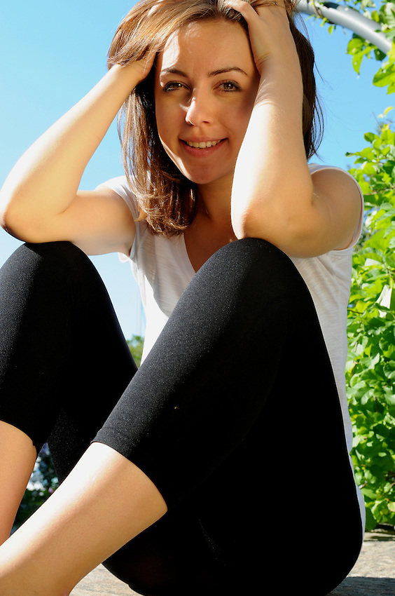 A beautiful young woman in yoga apparel sitting at Toronto Music Gardens