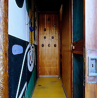 The entrance of Le Corbusier's Cabanon has a mural on one wall and painted doorknobs which act as clothes hooks