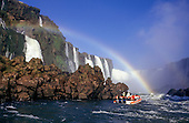 Iguassu Falls, Parana state, Brazil. Tourist inflatable boat approaching the falls with rainbow.