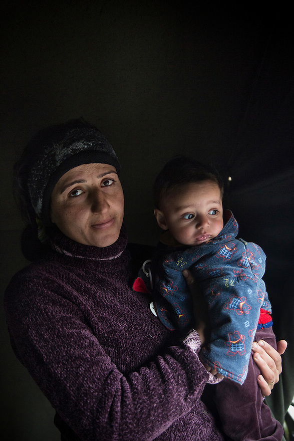 Halwa Hamo, wife of Rufat Alromi, with their first son, Imad. At the time Halwa was pregnant with their second son. They are Syrian Kurdish refugees from Al Hasakah, Syria. The family was sheltering at Harmanli Camp in Bulgaria. During the winter of 2013-2014, more than 1500 mostly Syrian asylum seekers were awaiting registration in subpar conditions, some living in tents, while others are crowded into unfinished buildings lacking sufficient hot water, electricity and food. Together with her husband and son, they moved to Germany after they were granted travel documents from Bulgarian authorities. After 8 months in Bulgaria they received travel documents and moved to Germany. They are currently living in Haan where their children are attending school.