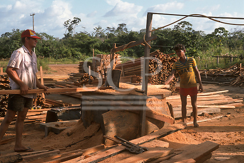 Para State, Brazil. Sawmill timber yard full of sawn timber; two men wearing flip-flops feeding wood through a planing machine covered in sawdust in the open air; large monkey wrenches on the ground - very untidy and dangerous.