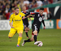 Chris Pontius (13) of D.C. United keeps the ball away from Chris Birchall (8) of the Columbus Crew during the game at RFK Stadium in Washington, DC.  D.C. United defeated the Columbus Crew, 3-2.