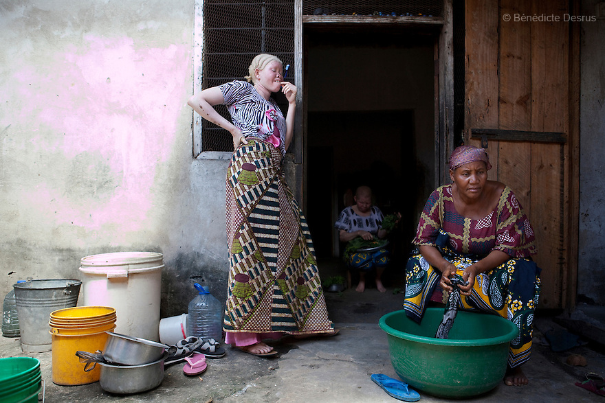 June 28, 2010 - Dar es Salaam, Tanzania - Mwajuma Ally (L), Ali's daughter and Ali's two wives at home. Ali Mohamed is a 61 year old Muslim man with albinism living in Tanzania where he has a shop selling rice and grains. Ali married his first wife, Jutia Jalehe, in 1978. Jutia is also an albino and together they had 1 son with albinism named Salehe Ally. In 1983, Mohamed married his second wife, Nuru Mohamedy who did not have Albinism. Together they had 6 children, two of them with albinism and four of them without albinism. Albinism is a recessive gene but when two carriers of the gene have a child it has a one in four chance of getting albinism. Tanzania is believed to have Africa' s largest population of albinos, a genetic condition caused by a lack of melanin in the skin, eyes and hair and has an incidence seven times higher than elsewhere in the world. Over the last three years people with albinism have been threatened by an alarming increase in the criminal trade of Albino body parts. At least 53 albinos have been killed since 2007, some as young as six months old. Many more have been attacked with machetes and their limbs stolen while they are still alive. Witch doctors tell their clients that the body parts will bring them luck in love, life and business. The belief that albino body parts have magical powers has driven thousands of Africa's albinos into hiding, fearful of losing their lives and limbs to unscrupulous dealers who can make up to US$75,000 selling a complete dismembered set. The killings have now spread to neighboring countries, like Kenya, Uganda and Burundi and an international market for albino body parts has been rumored to reach as far as West Africa. Photo credit: Benedicte Desrus