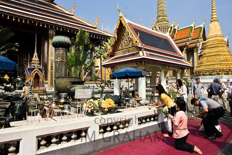 Tourists worship at the Royal Chapel of the Emerald Buddha, Bangkok, Thailand