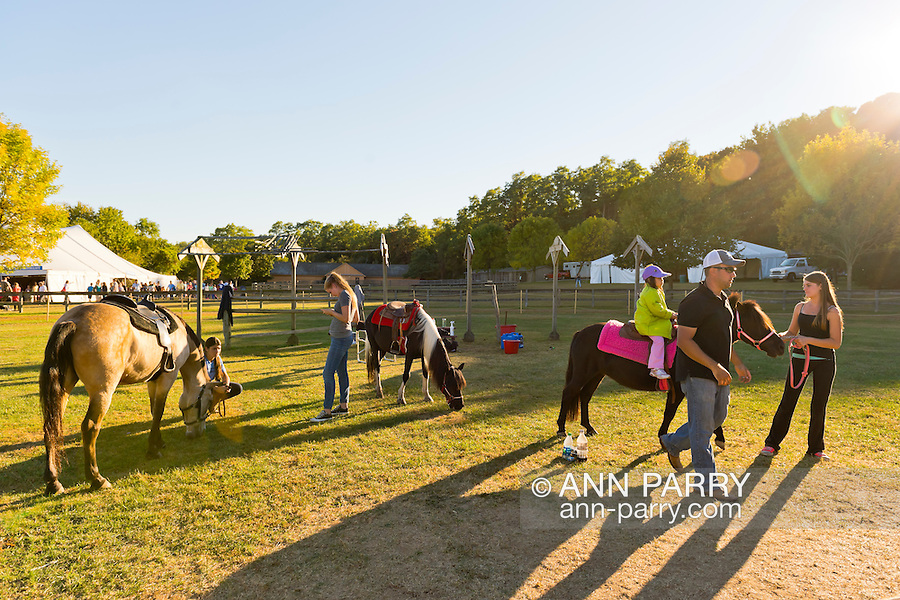 Old Bethpage, New York, U.S. 29th September 2013. The Pony Ride ias one of the last rides open as closing time arrives at The Long Island Fair. A yearly event since 1842, the county fair is now held at a reconstructed fairground at Old Bethpage Village Restoration.