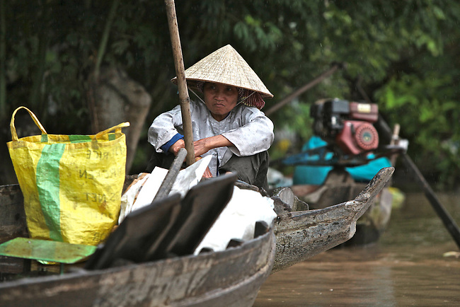 A woman selling fruit sits in her boat at the Cai Raing floating market, in the Mekong Delta, south of Can Tho, Vietnam. Sept.30, 2011.
