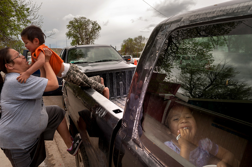 Shawna Black, left, helps son Joshua, 2, down from a pickup truck bed while Jaevonna Bellrock, 3 watches from inside the cab on the Crow Reservation at Crow Agency, Montana. Pending new ports for shipment to Asia through either the U.S. or Canada, Cloud Peak Energey hopes to open new high-grade coal mines on and near the Crow Reservation in southern Montana. The tribe is equally hopeful the new mines would bring long-awaited economic stability to the tribe. (Kevin Moloney for the New York Times)