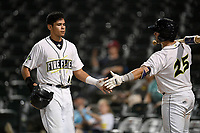 Center fielder Edgardo Fermin (10) of the Columbia Fireflies is greeted by Scott Manea (25) after scoring a run during a game against the Charleston RiverDogs on Tuesday, August 28, 2018, at Spirit Communications Park in Columbia, South Carolina. Columbia won, 11-2. (Tom Priddy/Four Seam Images)